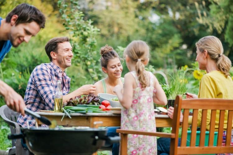 Famille autour d'un barbecue au jardin