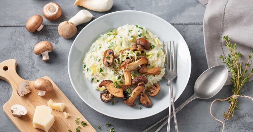Pilzrisotto auf einem Teller mit frischen Pilzen drumherum