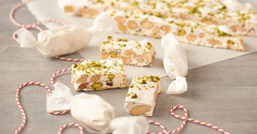 Weißer Nougat oder Turron mit Mandeln und Pistazien auf Backpapier